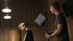 Two Men, One of Them is Singing to the Microphone. Music band rehearsal. Medium shot. Shot on RED Epic stock video