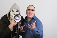Two men, one wearing a mask with megaphone Royalty Free Stock Images