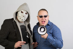 Two men, one wearing a mask, the other in sunglasses Stock Images