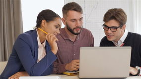 Two men and one woman look at the laptop. Two caucasian man and one black woman looking at the laptop. Afrrican american girl holding the pen near her chin