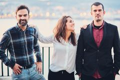 Two men and one woman are standing next to smile and joke, have fun. Friends laugh at the background of the evening city and the r. Two men and one women are Royalty Free Stock Image