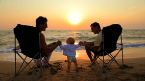 Two Men In Outdoor Chairs And Baby On The Beach At. This is a shot of two men in glasses and light summer clothes sitting in outdoor chairs holding hands with stock video