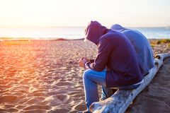 Two Men outdoor. Two Sad Men sit on the Log at the Beach royalty free stock photography