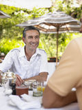 Two Men At Outdoor Table Chatting Stock Images