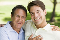 Two men outdoors embracing and smiling Stock Images