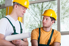 Two men in overalls and hardhat during work Stock Photography