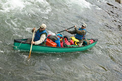 Two men in overloaded canoe on wild river rapids. Two men navigate an overloaded canoe through rapids during an adventure on a wild Alaskan river Royalty Free Stock Photography