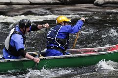 Two Men Paddling A Canoe On the Hudson River White Water Derby In North Creek In The Adirondack Mountains Of New York State. Two Men Paddling An Open Canoe In stock photos