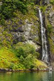 Two men paddling towards a waterfall on a Norwegian Fjord near the Village of Flam,. An action photo of two men paddling towards a waterfall on a Norwegian Fjord Stock Photography