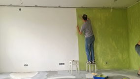 Two men painting a wall with roller. Time lapse video stock video