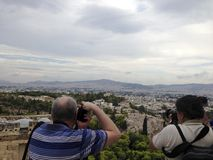 Two Men Paparazzi Reporters back turned take photos of a breathtaking landscape in Athens, Greece with their photography cameras stock image
