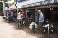 Two men park bikes in front of shop on the way to Myanmar. stock photo