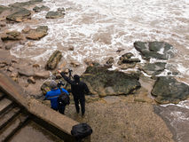 Two men photographing rough sea. Royalty Free Stock Image