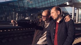 Two men on the platform of the railway station waiting for the arrival of the train and take pictures selfie on a stock footage