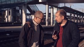 Two men on the platform of the railway station waiting for the arrival of the train, talking and excited about the trip stock footage