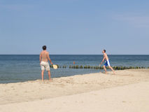Two men play beach tennis on the sandy coast of the Baltic Sea Stock Photography