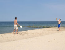 Two men play beach tennis on the sandy coast of the Baltic Sea Stock Photos
