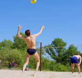 Two men play beach volleyball Stock Images