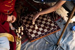 Two men play chess outdoors. Close up. Only hands can be seen stock photos