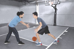 Two men playing basketball on the court Royalty Free Stock Image