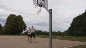 Two men playing basketball at outdoor. In summer day stock video