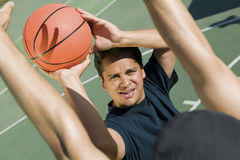 Two men playing basketball on a sunny day Royalty Free Stock Photography