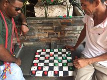 Two men playing checkers on street in Capurgana, Colombia stock photography