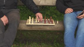Two men playing chess on bench in the park. In summer day stock video