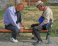 Two men are playing chess in park of Ulaanbatar. Ulaanbaatar, Mongolia - July 8, 2015: two men are playing chess in park of Ulaanbatar, Mongolia Stock Images