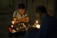 Two men playing Chinese chess. Hoi An, Vietnam - Sep 5, 2017: Two men playing Chinese chess on the sidewalk at full moon night in Hoi An ancient town, Vietnam Stock Photo