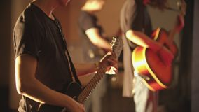 Two men playing electric and acoustic guitars at the performance. Mid shot stock footage