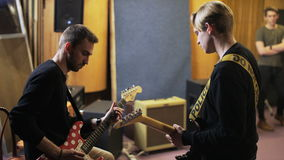 Two Men Playing Electric Guitars. Music band rehearsal. Medium shot. Shot on RED Epic stock video