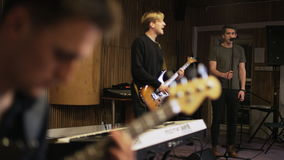 Two Men Playing Electric Guitars and a Vocalist Singing. Music band rehearsal. Long shot. Shot on RED Epic stock video