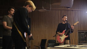 Two Men Playing Electric Guitars and a Vocalist Singing. Music band rehearsal. Medium shot. Shot on RED Epic stock video