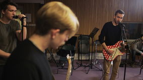 Two Men Playing Electric Guitars and a Vocalist Singing. Music band rehearsal. Medium shot. Shot on RED Epic stock footage