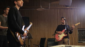 Two Men Playing Electric Guitars and a Vocalist Singing. Music band rehearsal. Medium shot. Shot on RED Epic stock video footage