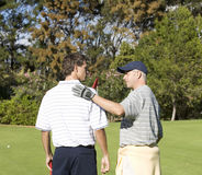 Two men playing golf Stock Images