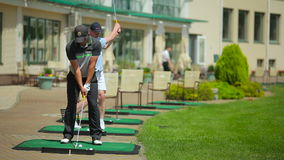 Two men playing golf near the clubhouse stock footage