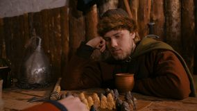 Two men playing popular strategy board game - tafl. Two men in russian ethnic suit playing medieval popular strategy board game - tafl. Folk, competition and stock video footage