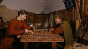 Two men playing popular strategy board game - tafl. Two men in russian ethnic suit playing medieval popular strategy board game - tafl. Folk, competition and stock video