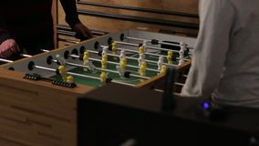 Playing Table Soccer. Two men playing table football yellow and white players foosball stock video footage