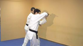 Two men practicing Aikido in the gym. Judo sport training in the sports hall stock video