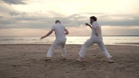 Two men practicing capoeira on beach. Two men in white clothes practicing capoeira on beach stock video footage