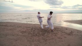 Two men practicing capoeira on beach. Two men in white clothes practicing capoeira on beach stock video