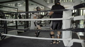 Two men practicing Muay Thai boxing. Two men practicing traditional Muay Thai boxing in the boxing ring with mirror surrounding. Men boxing traditional Muay Thai stock video