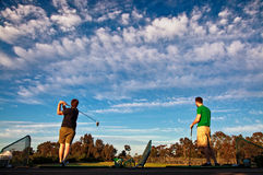 Two men practicing their golf swing at a driving range Royalty Free Stock Photos