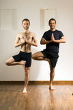 Two Men Practicing Yoga - Vertical Stock Photo