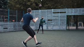 Two men practising American football on field. Slow motion of two men practising passing ball while playing American football on field stock footage