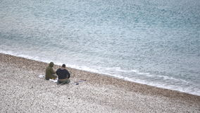 Two men are prepearing them fishing rod. On the beach stock footage