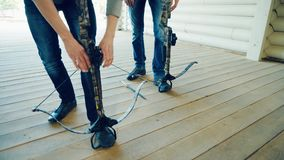 Two men pull the strings of the crossbows. Two men in jeans are pulling the strings of the crossbows in the shooting range stock video